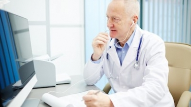 male doctor with earbuds on phone looking at computer screen