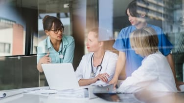 A group of four healthcare professionals sit around an open laptop and discuss among one another.