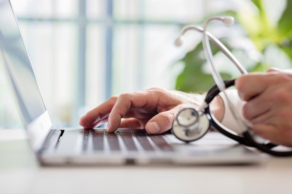 doctor entering patient notes on laptop