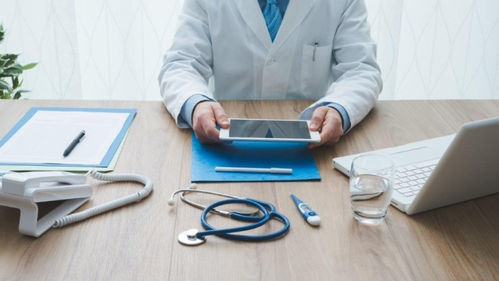 physician at desk with assorted technology