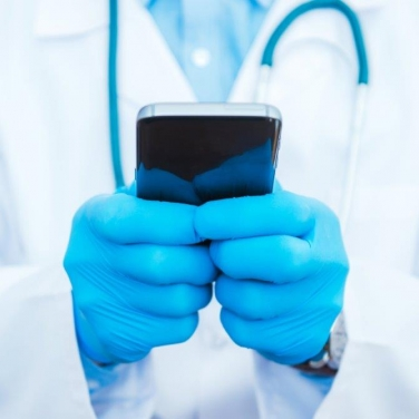Medical worker holding a smart phone with two hands