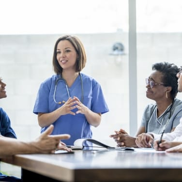 A number of healthcare professionals sit around a large table as one person stands and speaks.